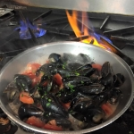 Prince Edward Island Mussels with diced Roma tomatoes in garlic white wine butter.