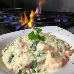 Shrimp Risotto - Fresh Georgia Shrimp sautéed with spinach, roasted red peppers and sweet Italian sausage tossed with risotto & garlic cream.