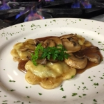 Homemade ravioli with a veal, spinach and ricotta cheese filling topped with Marsala mushrooms.