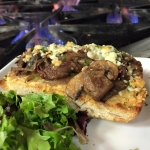 Bruschetta with braised beef and carmalized onions on rustic bread topped with Gorgonzola cheese.