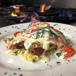 Asiago encrusted Grouper over parsley orzo with a Spinach and tomato cream Sauce.